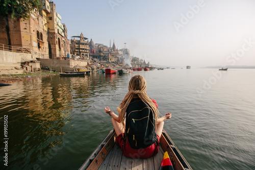 Podróżnicza kobieta jest ubranym dredy sadza w drewnianej łodzi i cieszy się widok Varanasi