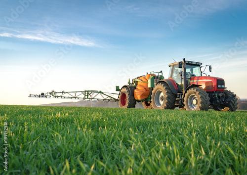 Photo  Unkrautbekämfung im Frühjahr, roter Traktor mit Feldspritze im jungen Getreidebe