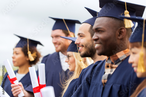 Photo education, graduation and people concept - group of happy international students