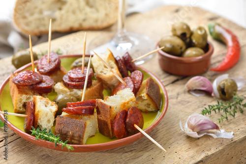 Foto auf AluDibond Bar Spanische Pinchos: Angebratene scharfe Chorizo Paprikasalami auf geröstetem Weißbrot serviert