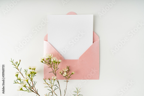 Fototapeta Minimal composition with a pink envelope, white blank card and a wax flower on a white background. Mockup with envelope and blank card. Flat lay. Top view. obraz