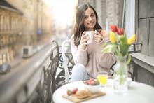 Sweet Girl Having A Delicious Breakfast On The Balcony