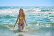 Young beautiful slim woman in bikini on sunset beach. Having fun in sea with a lot of splashes