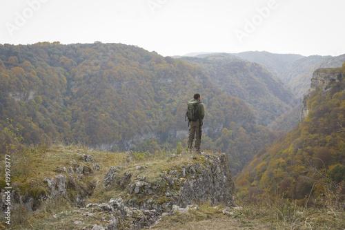 Fotomural молодой парень смотрит на красивое горное ущелье