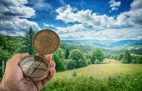 Photo Compass in the hand against mountain background