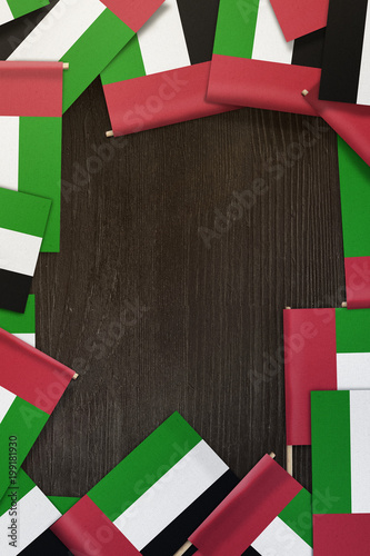 Fotografie, Obraz  United Arab Emirates small flags framing a wood texture background with copy spa