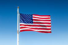USA Flag Waving In The Wind Against Blue Sky On A Sunny Day