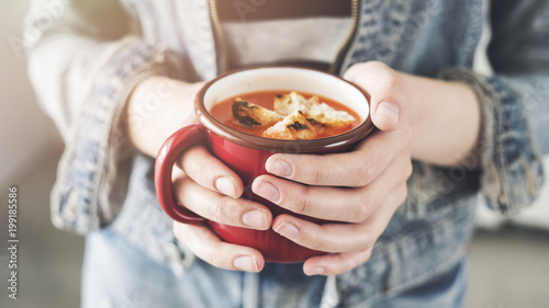 Woman holding tomato soup cup