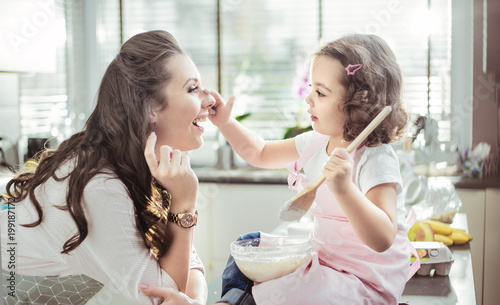 Pretty mother and her daughter preparing a cake