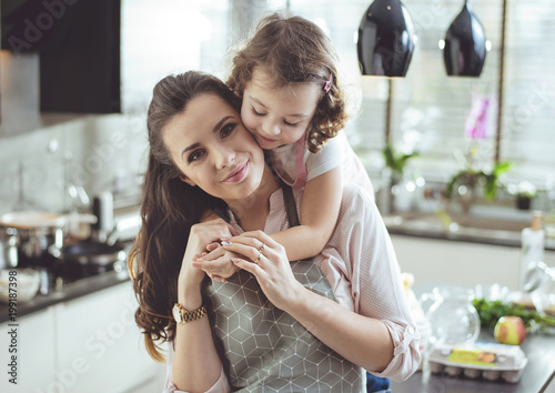Portrait of a cute daughter hugging her mother