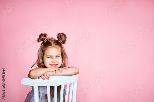 Photo  cute little girl sits on a white chair smiling and looks at the camera on a pink