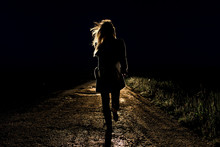 Lonely Young Frightened Woman On An Empty Night Road Runs Away In The Light Of The Headlights Of Her Car