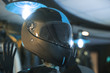 Black fashion carbon motorcycle helmet with blue insets on the shelf in the shop