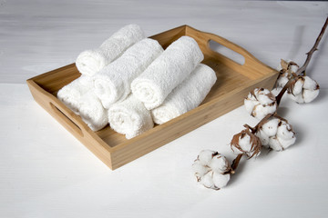 Fototapeta na wymiar tray with a towel for hand in spa salon and a cotton branch on a white wooden table