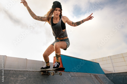 Cool young woman skateboarding at skate park