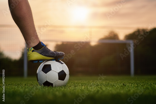 Photo  Soccer ball with player in the sunset, soccer gate in the background