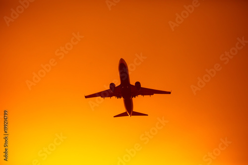Fotobehang Vliegtuig flying airplane silhouette in the orange sky sunset