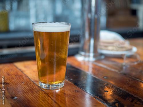Full pint glass of beer sitting on bar counter Wallpaper Mural