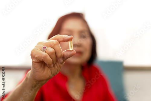 Fotografie, Obraz  Senior woman hand holding vitamin fish oil and looking at camera with relief