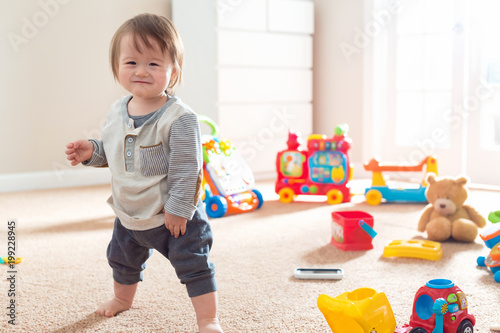 Toddler boy in his playroom surrounded by toys Canvas Print