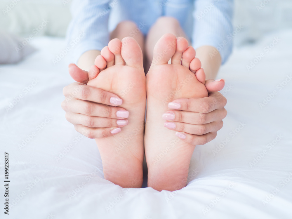 Fototapety, obrazy: Young woman massaging her foot on the bed., Healthcare concept.