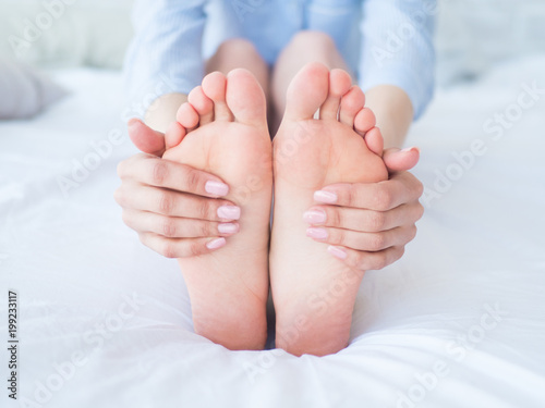 Fotografía  Young woman massaging her foot on the bed., Healthcare concept.