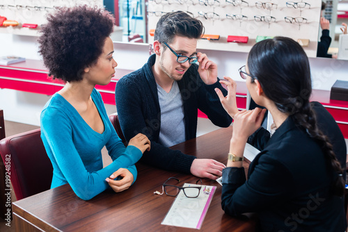 Papiers peints Statue Woman and man buying glasses at optician store getting advice from saleslady