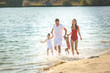 Happy family having fun at the beach. Mom, dad, son and little daughter at the sea shore. Cheerful family