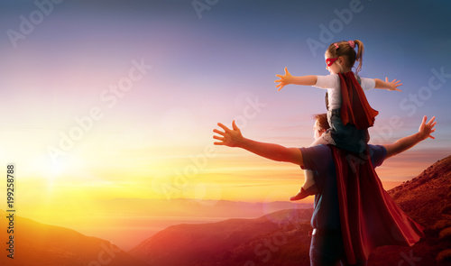 Obraz Daughter And Her Father Dressed As Heroes Watching The Sunset  - fototapety do salonu