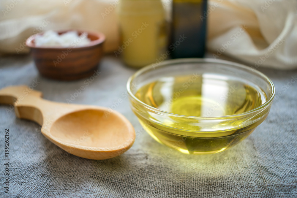 Fototapeta Liquid coconut MCT oil in round glass bowl with wooden spoon and bottles. Health Benefits of MCT Oil. Triglycerides, a form of saturated fatty acid