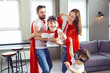 Happy family in superhero costumes playing together in a room.