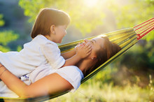 Girl In A Hammock Playing With Happy Mom's Face