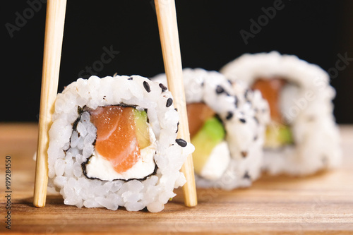 Fototapeta Macro shot of sushi, sashimi, uramaki and nighiri. typical Japanese dish consisting of rice, salmon or tuna,shrimp and fish eggs soaked in soy. Concept: Japanese restaurant, sushi, oriental tradition. obraz