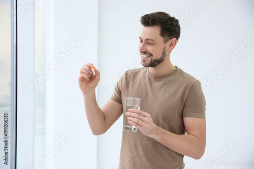 Fototapeta Young man taking vitamin indoors obraz