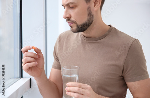 Fototapeta Young man taking pill indoors obraz