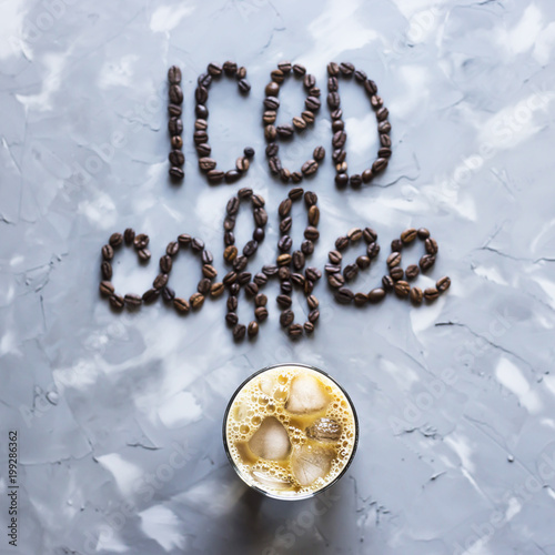 """Fotografie, Obraz  A glass of iced coffee with milk next to the inscription """"ice coffee"""" from coffee beans on a gray concrete background"""