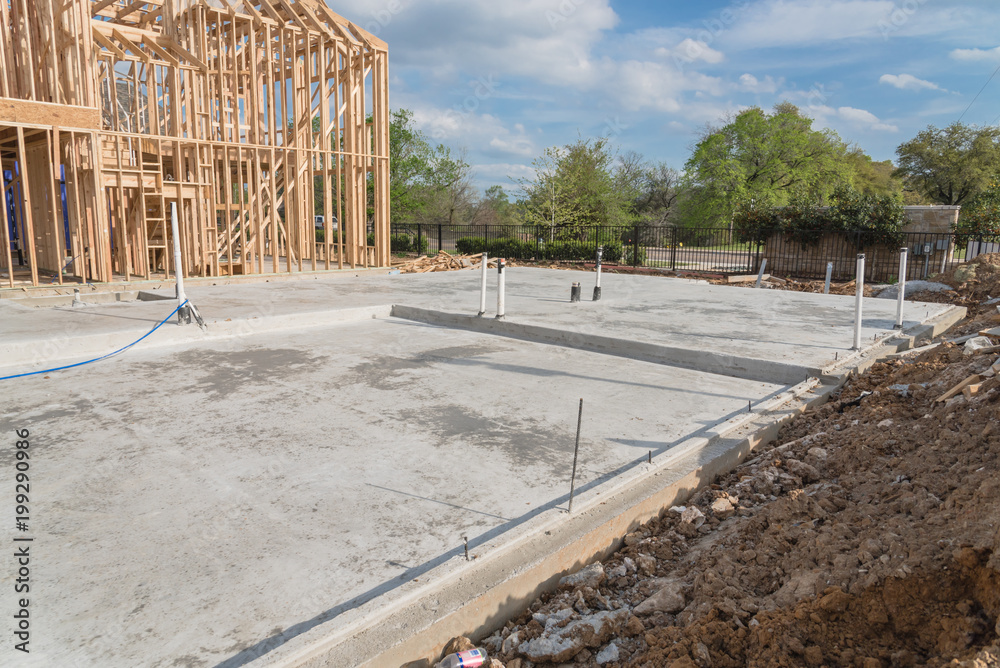 Fototapeta Slab-on-grade foundation footing timber frame house under construction in Irving, Texas, USA. Shallow raft structural engineering transfers building loads to earth very near to surface, pile of earth