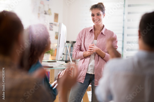 young woman presenting project. she is applauded by colleagues Wallpaper Mural
