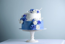 Beautiful Two Tiered White And Blue Wedding Cake Decorated With Flowers Sugar Roses. Concept Of Elegant Holiday Desserts