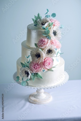 Beautiful three tiered white wedding cake decorated with flowers sugar pink peonies. Concept of elegant holiday desserts