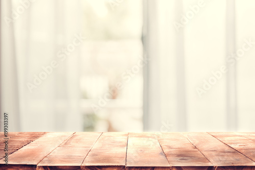 Defocused curtain window and empty of wood table top with warm sunlight Wallpaper Mural