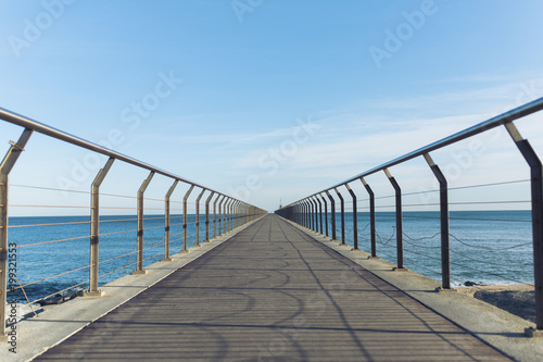 Diminishing perspective of pier over sea against sky