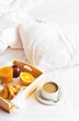 Morning breakfast in bed wooden tray with a cup of coffee croissant orange juice fresh orange jam Bed linen. Top view Hotel Room Early Morning at Hotel Background Concept Interior Copy Space