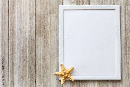 Mockup with white frame and star fish on a rustic wooden background ...