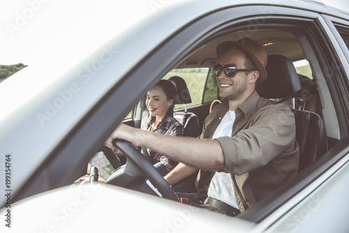 Valokuva  Joyful young man in sunglasses is driving his car while traveling with his girlfriend across the country