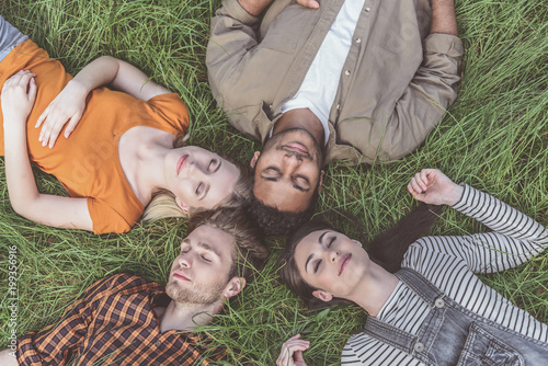 men and women lying on grass with eyes closed. They are tranquil and satisfied. Top view portrait