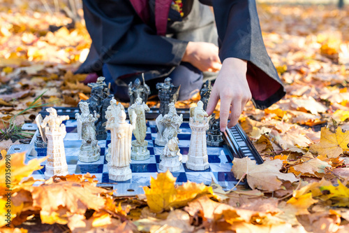 cute boy in costume makes fun face, plays chess and reads book in autumn park, wizard, cosplay