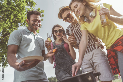 mata magnetyczna Cannot wait. Low angle of hungry people standing near barbecue and smiling. They are holding beer and taking roasted snacks