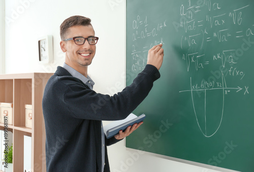 Fotografía Young male teacher writing on blackboard in classroom