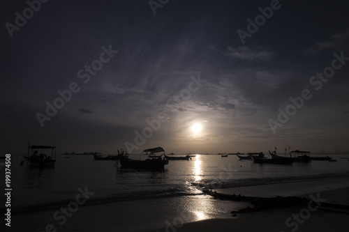 A beautiful sunrise near the beach with boats surround it in Penand Malaysia early in the morning